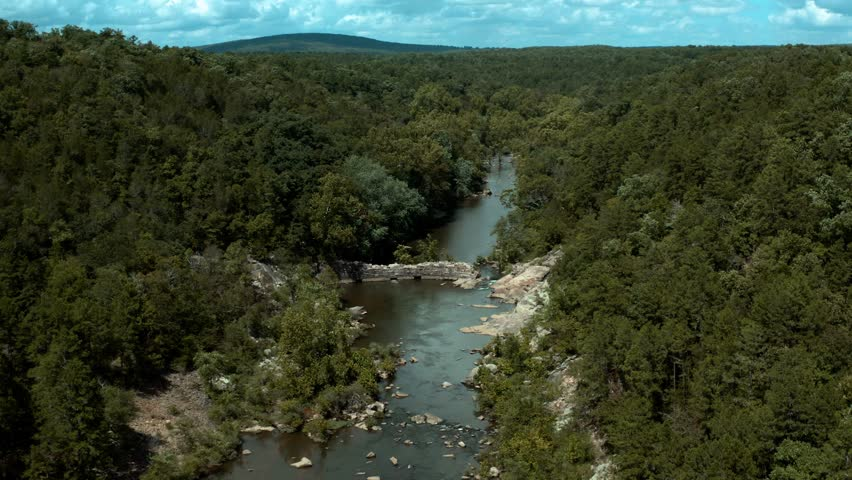 Aerial View of Flowing River, Stream or Creek with swimmers at rock dam, water rapids, rock formations, green shores and trees