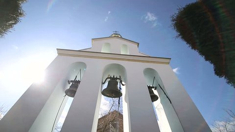 Church bells on a Sunny day in a strong wind. The wind shakes the trees near the bell tower and Sonechka shines in the cell near the Church bells