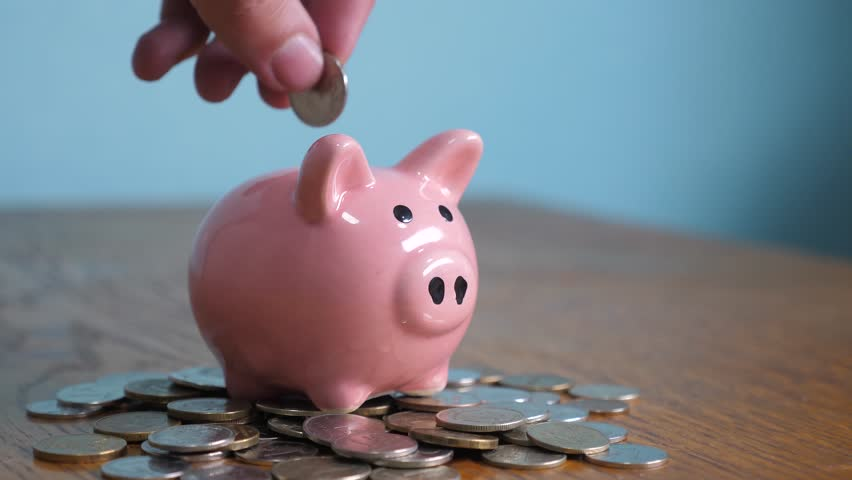Piggy bank business standing on a pile of coins concept. A hand is putting a coin in a piggy bank on lifestyle a yellow background. saving money is an investment for the future. Banking investment and | Shutterstock HD Video #1025625953