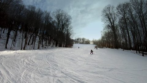 Skiers and snowboarders going down the slope and making turns. People having fun skiing and snowboarding on a groomed trail. Beautiful Vermont winter vacation. Wide shot.