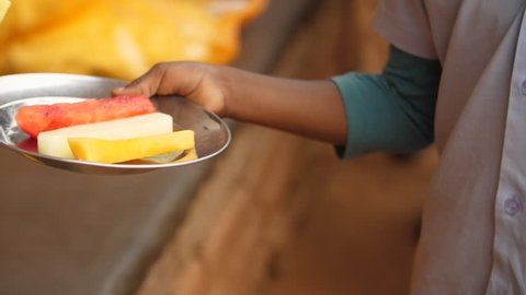 Young African school pupil receives fruit in plate for lunch program