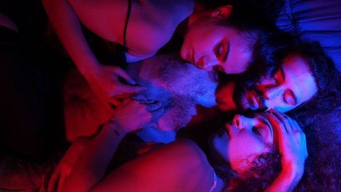 Three young people kissing in bed.Polyamory,Poligamy,Threesome