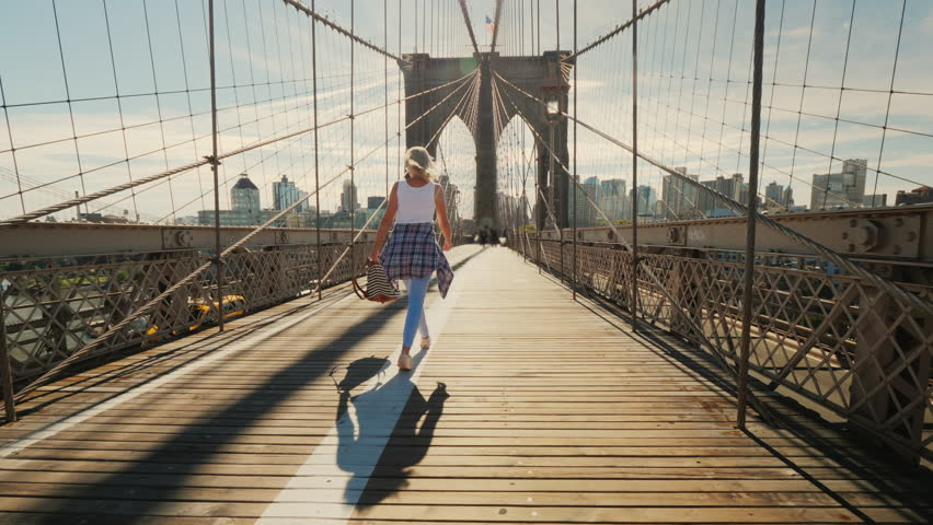 Active young woman walks on the Brooklyn Bridge in New York | Shutterstock HD Video #1025688323