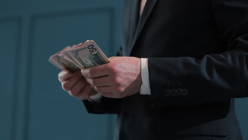 Businessman counting dollar banknotes. A business deal with the transfer of money. Close-up of man gives a stack of dollars to girls. | Shutterstock HD Video #1025691683