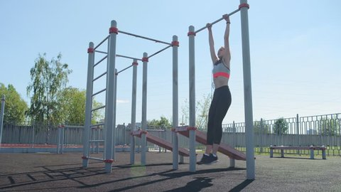 Fit girl in sports bra and tights doing warm-up routine at outdoor workout station: doing abs twists hanging on pull-up bar and standing on ground, performing bends exercise and body circles
