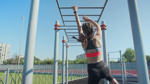 Back view of athletic teenage girl doing monkey bars climbing exercise and recovering after it at street workout spot, fitness tracker on her wrist