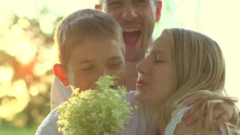 Happy family. Father, Mother and their little son with bouquet of flowers outdoors. Mom, dad and kid kissing and hugging. Mother's day gift. Slow motion, high speed camera shot. Full HD 1080p
