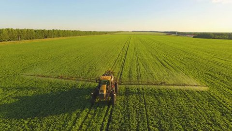 Tractor spraying pesticides on soybean field with sprayer at spring. Aerial Quadcopter Shooting