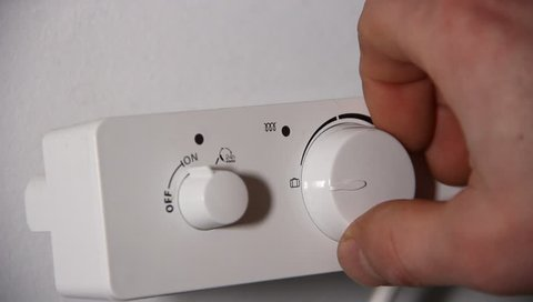 close up of man hand adjusting temperature in the bathroom