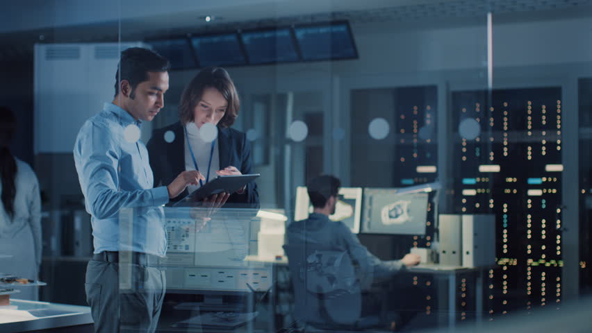 In Technology Research Facility: Female Project Manager Talks With Chief Engineer, they Consult Tablet Computer. Team of Industrial Engineers, Developers Work on Engine Design Using Computers | Shutterstock HD Video #1025738153