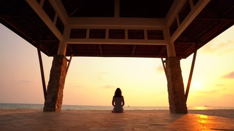 The girl is making yoga pose in a Buddhist temple at sunset.