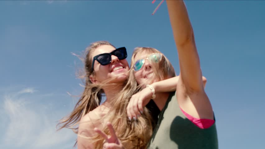Two young joyful cheerful girls taking a selfie near airport with huge airplane flying over their heads.Best friends taking photos against sky background.Tourism,destination and friendship concept | Shutterstock HD Video #1025748113