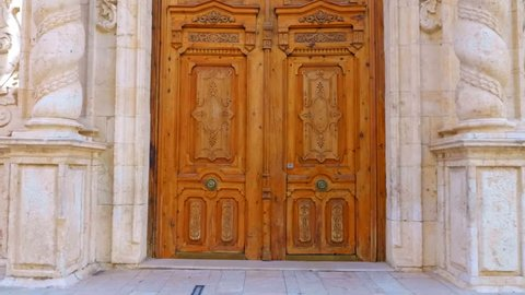 Entrance with a big wooden door in to beautiful ancient church with twisted columns and ornate decorated facade in the Spain city. Shot in motion
