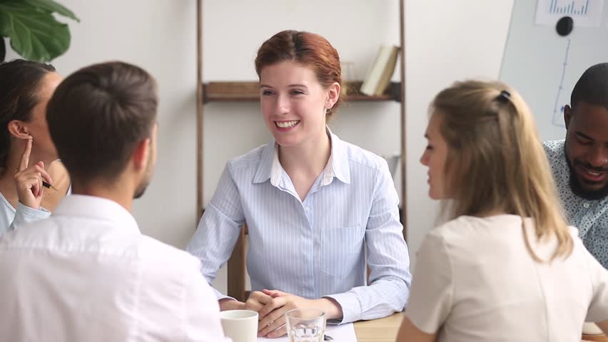 Happy female boss manager thank male worker finish group meeting, smiling friendly business leader talking make deal with client handshake employee promoting appreciating at diverse team negotiations