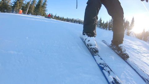 Super slow motion shot of Skiing. Ski resort in the snowy mountain woods on a bright winter day. Legs view of young man on ski slope. Winter sport, travel and vacation concept.