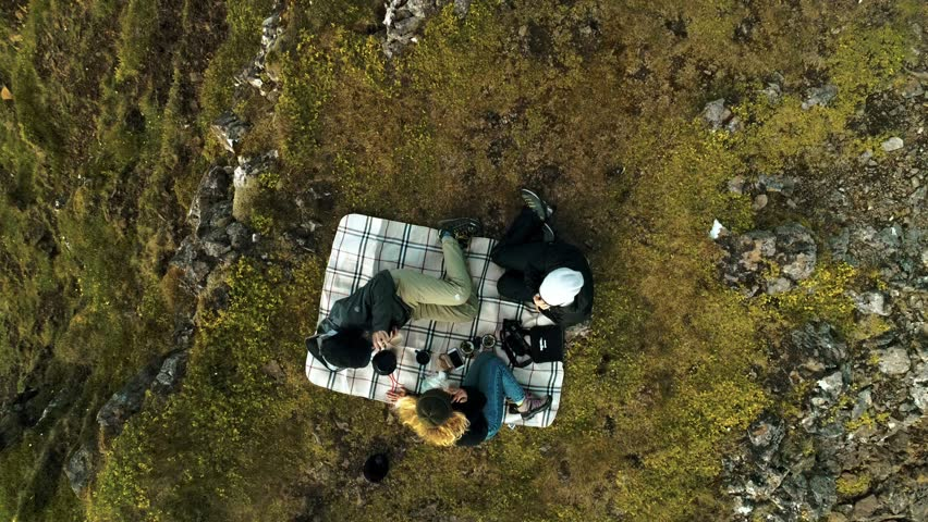 Straight down zoom out drone shot of friends on picnic on authentic quilt blanket on edge of epic cliff or rock during hiking or trekking adventure trip in wild nature. Millennial outdoors lifestyle | Shutterstock HD Video #1025887853