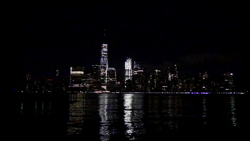 Still shot of the NYC skyline at night from the bay with shimmering lights dancing on the water | Shutterstock HD Video #1025898653