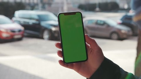 Lviv, Ukraine - May 19, 2018: Slow motion woman holding phone with vertical green screen in the background moving car man chroma key technology use mobile internet message smart sunset cell