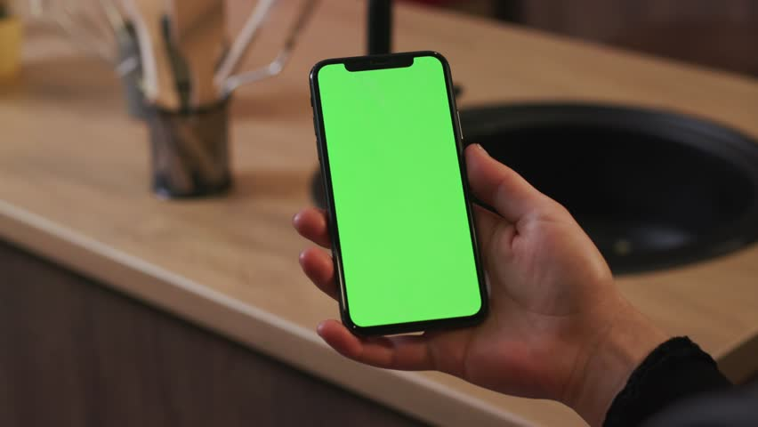 Tokio, Japan - April 7, 2018: Woman hand hold use smartphone with vertical green screen on kitchen at home breakfast browse business food girl house shopping healthy internet abstract slow motion | Shutterstock HD Video #1025899403