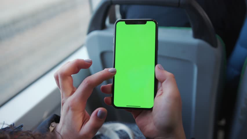 Lviv, Ukraine - May 19, 2018: Slow motion woman's hand holding a mobile telephone with a vertical green screen in tram chroma key smartphone technology cell phone street touch message display hand | Shutterstock HD Video #1025899463