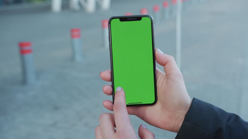 NEW YORK - April 5, 2018: Woman holding use touch phone with vertical green screen on busy street pavement scrolling pages swiping surfing internet technology smartphone chroma key message slow motion | Shutterstock HD Video #1025899493
