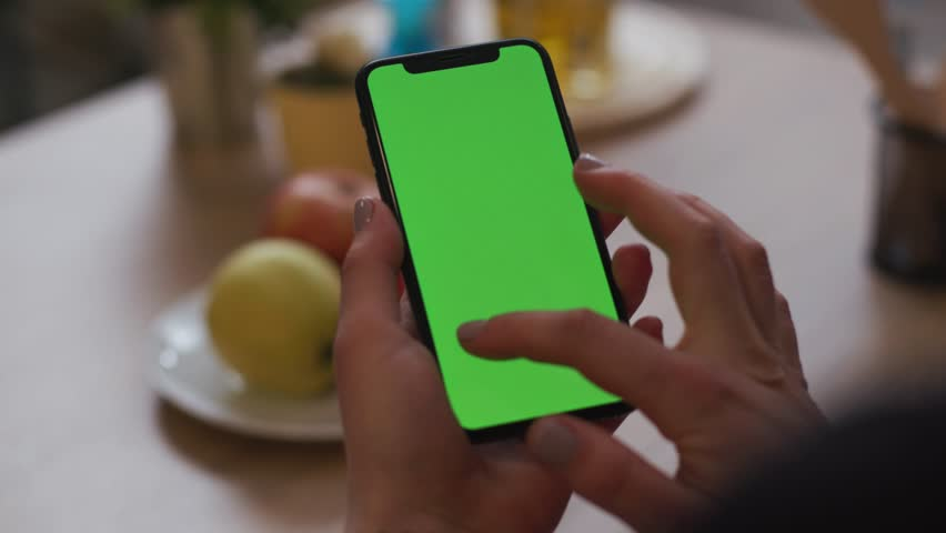Tokio, Japan - April 7, 2018: On kitchen woman hand hold use smartphone with vertical green screen at home breakfast browse business food girl house shopping healthy internet abstract slow motion | Shutterstock HD Video #1025899523