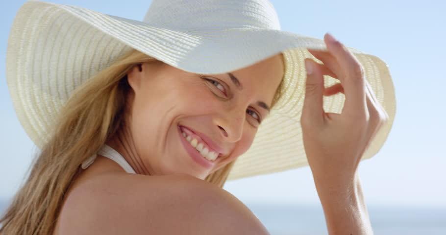 Beautiful woman walking on beach looking back at camera smiling steadicam slow motion shot RED DRAGON