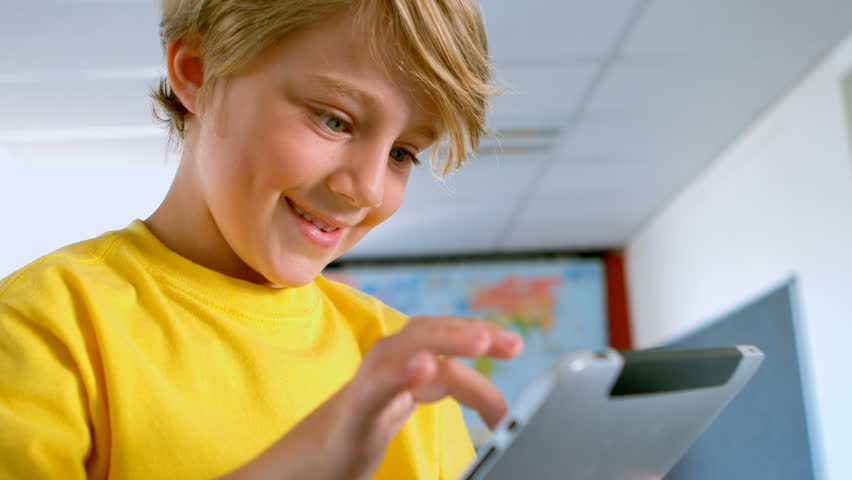 Side view of happy Caucasian schoolboy using digital tablet in a classroom at school. He is studying and learning 4k | Shutterstock HD Video #1025908343