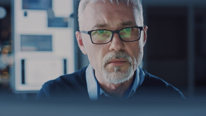Portrait of Handsome Middle Aged Engineer Wearing Glasses Works on Personal Computer. In the Background High Tech Engineering Facility. Shot on 8K RED Camera. | Shutterstock HD Video #1025971223