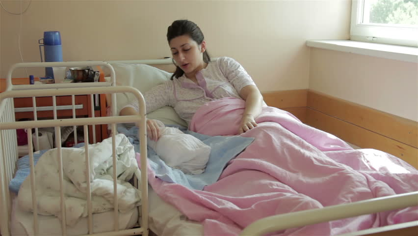 nurse talking with mother who is sitting on bed with
