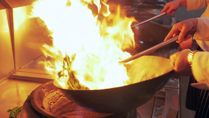 Slow motion of Chef Cooking in the Kitchen, Restaurant wok fire cooking Close up, cook frying vegetable in the commercial kitchen. Chinese style Sichuan food cooking 4k clip | Shutterstock HD Video #1025994413