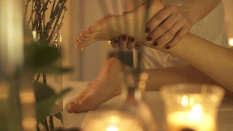 A thai masseur slowly massaging feet with oil.