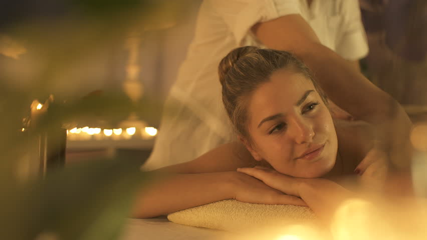 Woman enjoying body massage at spa club. | Shutterstock HD Video #1026016553