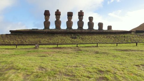 Zoom-out shot of the Moai stone head statues. Heads with hat-like additions facing inland of the island. Easter Island, Chile.