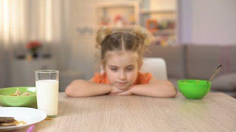 Female kid refusing to eat broccoli, throwing vegetable away, vitamin nutrition