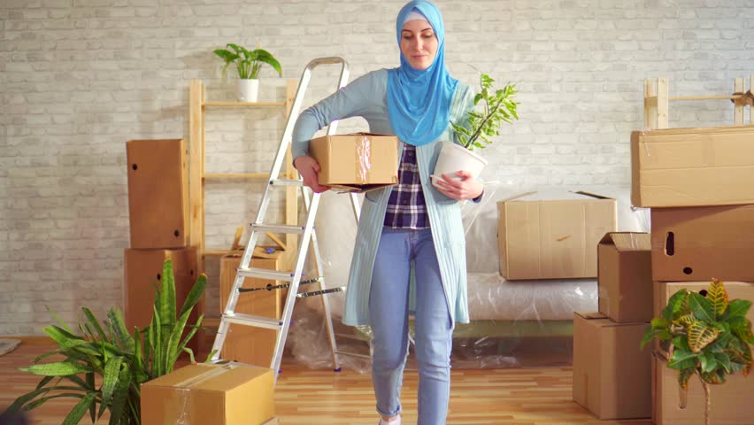 Portrait young muslim woman in a hijab with a flower and a box in her hands | Shutterstock HD Video #1026227393