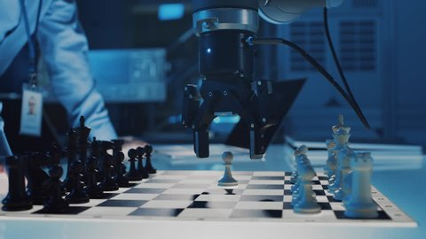 Close Up Shot of a Artificial Intelligence Operating a Futuristic Robotic Arm in a Game of Chess Against a Human. Robot Moves a Pawn. They are in a High Tech Modern Research Laboratory.