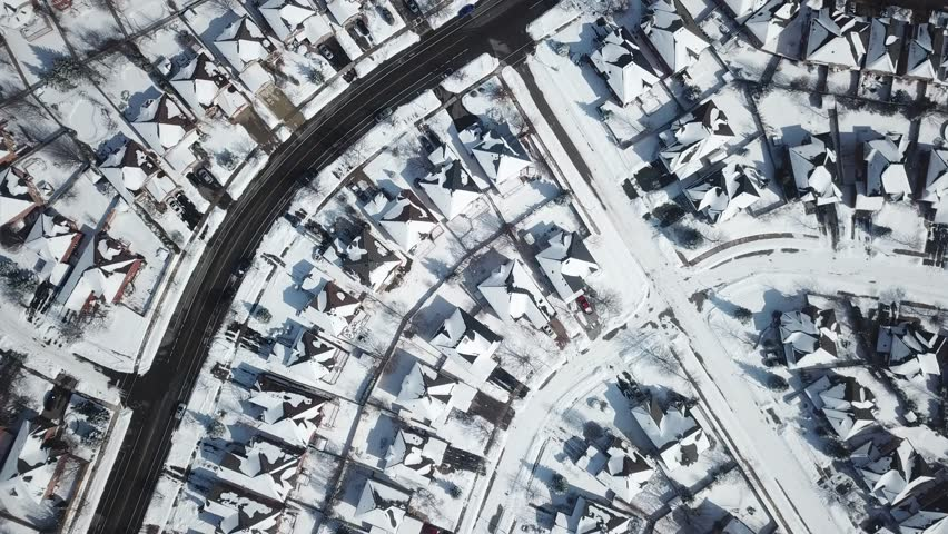 Aerial drone footage of a suburban community in Canada after a blizzard snow storm.  Snow fills the field of view and everything is coated in white. #1026261473