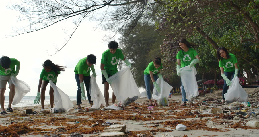 Group of young asian people volunteers in green t-shirts cleaning up the beach with plastic bags full of garbage. Safe ecology concept. 4k resolution. | Shutterstock HD Video #1026301043