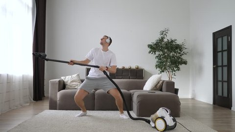 Young Cheerful Man Dancing With Vacuum Cleaner While Cleaning The Room