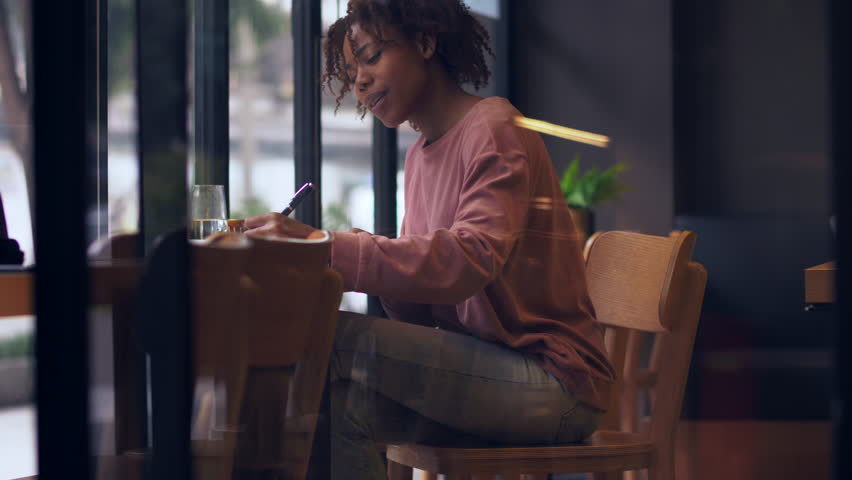Side view of one pretty young African woman writing a letter by the window, a joyful left handed black young female freelancer working in the cafe writing notes. Young people working and study 4k clip | Shutterstock HD Video #1026314033