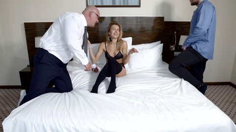 Two handsome guys and one naked sexy girl in bed of a hotel room, starting threesome.