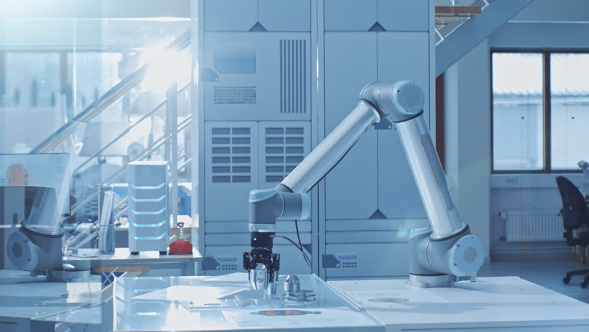 In the Bright Robotic Industry Engineering Facility Robot Arm Picks Up Metal Component Moves it Into Place. High Tech Industrial Technology Using Modern Machine Learning, Data Mining