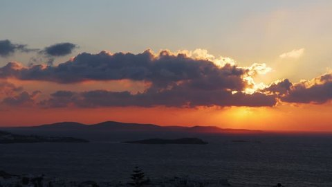 Timelapse shot, of clouds and the orange sun,ing above islands and the mediterranean sea, on a sunny evening, in Santorini, Greece, Europe