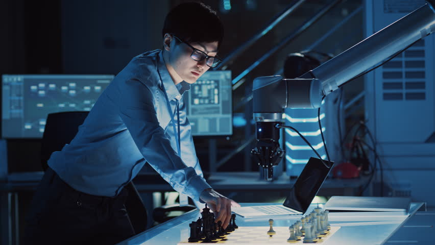Professional Japanese Development Engineer is Testing an Artificial Intelligence Interface by Playing Chess with a Futuristic Robotic Arm. They are in a High Tech Modern Research Laboratory. | Shutterstock HD Video #1026410213