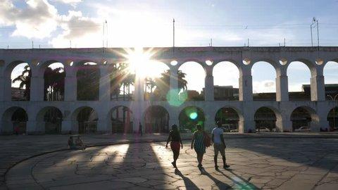 Rio de Janeiro, Brazil - March 26, 2019: Carioca pedestrians with sunrays backlighting 19th-century colonial Lapa Arches, Rio de Janeiro, Brazil - 4K