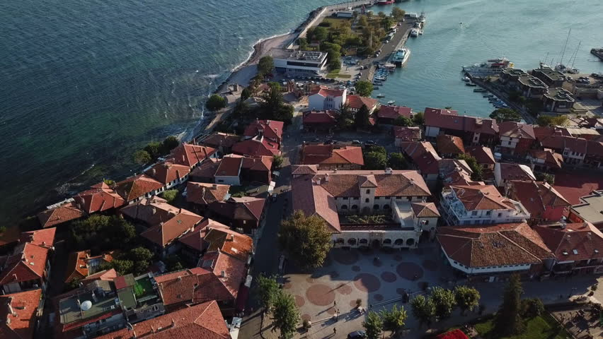 Flying over, aerial view of old Nessebar, ancient city on the Black Sea coast of Bulgaria, UNESCO World Heritage, port with fishing boats