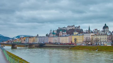 Watch historical Salzburg city center from the bridge across the Salzach river, overlooking Hohensalzburg fortress, edifices on embankments and Alps, surrounded by heavy rainy clouds, Austria.