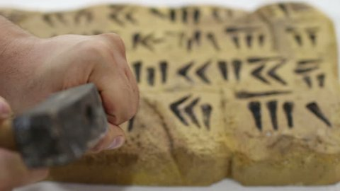 Ancient cuneiform writing by a man using a hammer and chisel