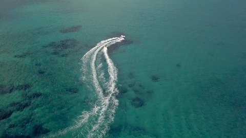 A speedboat swerves and maneuvers while pulling a tube and passenger; Paros island, Greece; Aegean Sea; aerial drone.